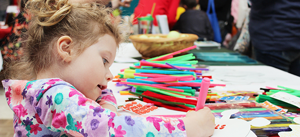 Preschool student practices coloring at an early childhood event