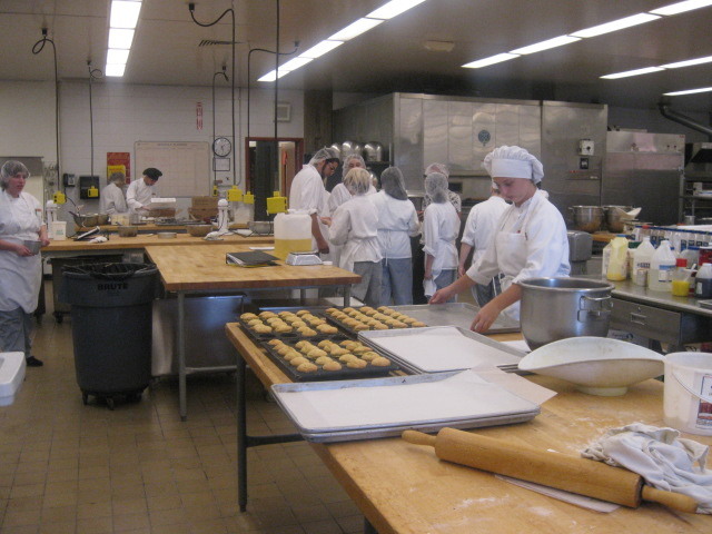 This is a photo of high school culinary students working in a kitchen.