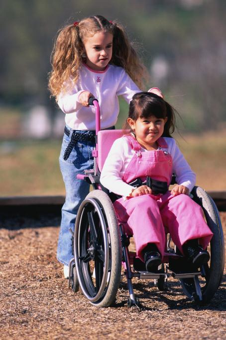 girl pushing friend in wheelchair
